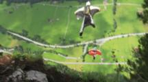 Two Men In Wing Suits Jump From A Cliff.