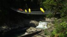 Group Of Kayakers Walking Across A Rope Bridge With Their Gear.