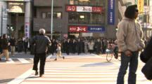 Wide Shot Of A Massive Group Of Japanese People Crossing A Big City Street.