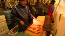 Close Up Of A Man Chopping Up Raw Fish In A Fish Market.