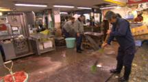Men Cleaning Up The Fish Market With Water And Brooms.
