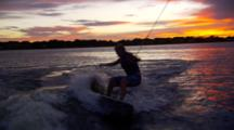 Wakesurfer Riding Behind A Boat At Sunset