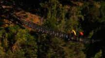 People With Kayaks Walking Across A Rope Bridge.