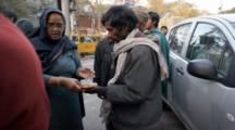 Man And Woman Giving Out Food On Street