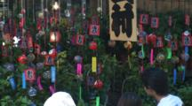 Wind Bells In Breeze Displayed On Busy Street