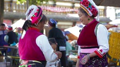 Woman in Traditional Clothing Weighting a Fish, Dali, Yunnan, China
