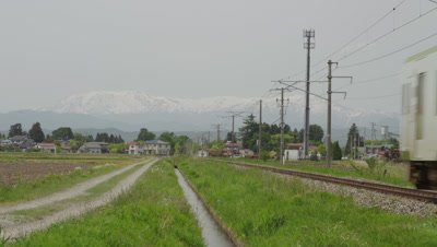 Diesel passenger train passing through countryside on the Banetsusaisen Line in Japan
