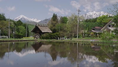 Hakuba mountains reflected on surface of rice paddy in Japan