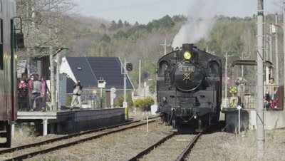 Steam locomotive stop at station with black smoke blowing in Japan