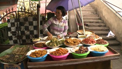 Woman preparing dishes at food stand in Bali, Indonesia
