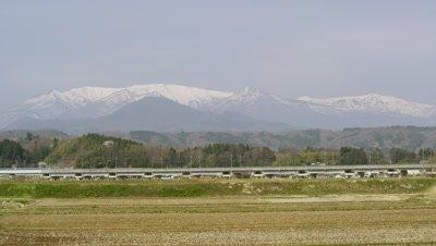 Tohoku Shinkansen Hayabusa traveling with Zao Mountain Range in background, Miyagi Prefecture, Japan