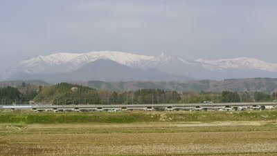 Tohoku Shinkansen traveling with Zao Mountain Range in background, Miyagi Prefecture, Japan