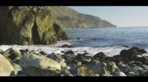 Beach View Of The Ocean Surge Along A Rocky Shore With Coastal Cliffs, Blue Sky. Cine-Slider Shot.