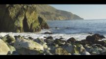 Beach View Of The Ocean Surge Along A Rocky Shore With Coastal Cliffs, Blue Sky. Cine-Slider Shot.