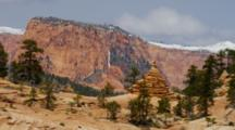 Spire Like Eroded Rock Formations Against Snow Capped Mountains Of Red Rocks, Utah.
