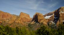 Pan From Right To Left. Snow On Red Rock Mountains, Pine Forest In Front. Zion National Park, Utah