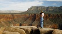 Grand Canyon Rim, Showing The Eroding Rock Layers At The Rim, Karen Ward Photographing The Canyon Below. Arizona.
