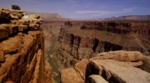 Red Rock Formations On The Rim Of The Grand Canyon With The Colorado River. Shot Pans Right To Left.