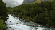 Blue Mountain River Flowing Lt To Rt With White Cascades Up Stream To Mountains, Pan Downstream To Close Up Cascades.