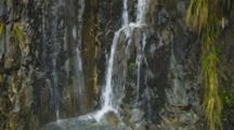 Waterfalls Off Vegetated Steep Cliff Into Crystal Blue Rocky Pool. Pan From Base To Top. South Island, New Zealand.