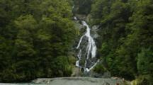 Medium Shot Of Waterfall Streaming Through Rainforest, With Rocky Riverbed In Foreground. Rain Is Falling. South Island, New Zealand.