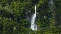 Waterfall Pouring Off Cliff Through Rainforest, Mist Blows To Left. South Island, New Zealand.