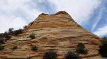 Dome Of Red Rock, Layered And Covered In Shrubs, With Blue Sky And Clouds. Zion National Park, Utah.