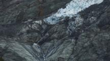 Glaciers Cling To The Steep Mountains Of The Southern Alps. Water Flows From The Base Of The Glacier.