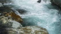 Shot Pans Upstream. Haast Pass, River Rushing Over Rocky Canyon, Aqua Blue Fresh Water.
