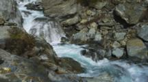 Shot Pans Downstream. Haast Pass, Tight Shot Of River Rushing Over Rocky Canyon, Aqua Blue Fresh Water.