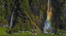 Waterfall With Multi-Colored Rainbow Streams Down Rocky Cliff With Thick Vegetation. Second Waterfall To The Left.