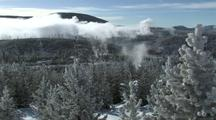Snowy Pines, Steam, And Clouds