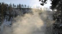 Steam Rising In Front Of Trees And Snowy Hillside In Sunlight