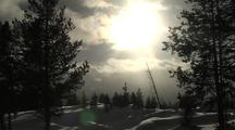 Clouds Move In Front Of Sun Over Snowy Landscape With Trees