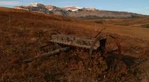 Tight Shot Of Old Wagon Wheel Spokes, Camera Pulls Back To Reveal Rest Of Wagon, Plains With Fall Colors, And Mountains In Background