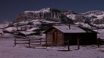 Camera Zooms Out From Antlers Hanging Over Snow Covered Cabin Door To Reveal Cabin And Surrounding Area. Everything Dusted With Snow With Mountains Rising In The Background.