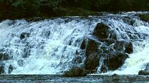 Clip Starts At Close Up Of Waterfalls, Camera   Then Zooms Out To Show Surrounding Area.