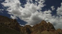 Time Lapse Of Clouds Over Red Rocks, Nevada. Steep Desert Mountains Go In And Out Of The Clouds' Shadows.
