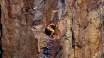 Person Rock Climbs Up Sheer Cliff Face