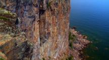 Extreme Wide Angle, Person Rock Climbs Up Sheer Cliff Face With Lake Below