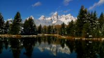 Rugged Teton Mountain Range Rises Above Tree-Lined Snake River In Autumn