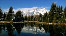 Pine Trees And Teton Mountain Range Reflected In Snake River