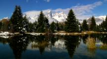 Pine Trees And Teton Mountain Range Reflected In Snake River
