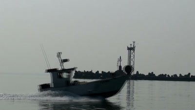 Fishing boat returning to harbor passing in front of camera