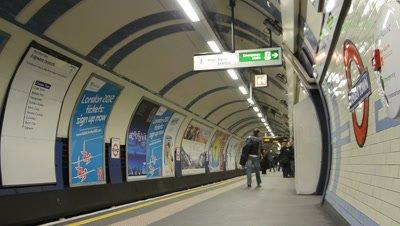 train passes pedestrians at Camden Town underground station,London