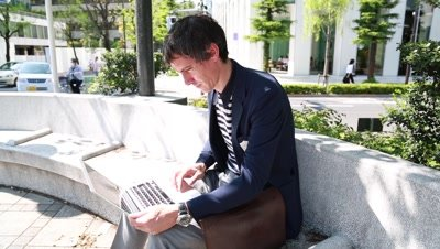 Caucasian businessman using laptop computer outside in Tokyo