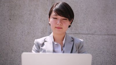 young Japanese businesswoman works on laptop computer, Tokyo