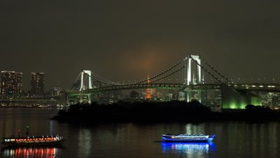 Time lapse night view of Rainbow Bridge and Tokyo Tower with cityscape in the background from Odaiba,Tokyo