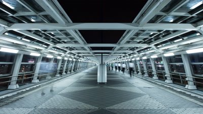 Time lapse night view of futuristic pedestrian passageway with people walking in Odaiba,Tokyo,Japan