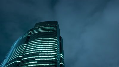 Time Lapse night view of the Shiodome skyline at night with clouds moving fast in front of the full moon,Tokyo,Japan